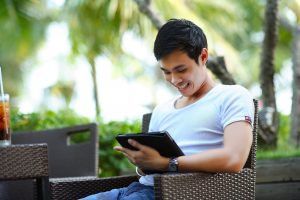 Man Sitting Outside On Tablet