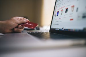 Person Holding Credit Card Next To Laptop